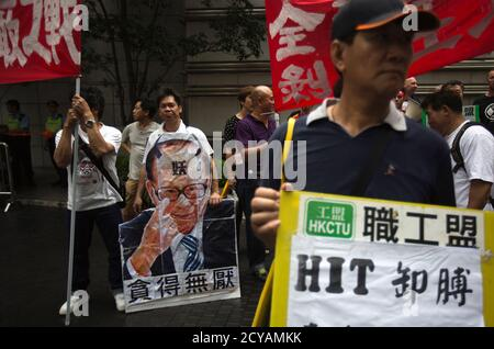 A dock worker holds a defaced picture of Hong Kong's tycoon Li Ka-shing as he marches during a strike, outside Cheung Kong Center in Hong Kong April 17, 2013. Striking dock workers at a port operator backed by Li failed to reach a deal for higher pay, prolonging a dispute that could cost the city its position as the world's third-largest container port. The word on Li's forehead reads, 'Evil' while those below his picture reads, 'Unlimited greed' REUTERS/Tyrone Siu (CHINA - Tags: BUSINESS EMPLOYMENT CIVIL UNREST) - Stock Photo