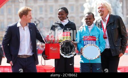Britain's Prince Harry (L) and Virgin CEO Richard Branson (R) pose on the podium with London Marathon winners Tsegaye Kebede of Ethiopia (2nd R) and Priscah Jeptoo (2nd L) of Kenya on the Mall in central London, April 21, 2013.  REUTERS/Andrew Winning (BRITAIN - Tags: SPORT ATHLETICS ROYALS ENTERTAINMENT SOCIETY) - Stock Photo