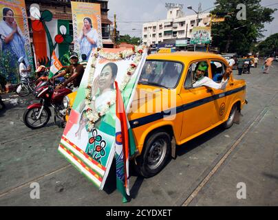 A man drives an iconic yellow ambassador taxi with a portrait of Trinamool Congress party leader Mamata Banerjee attached to the front in a street in Kolkata, May 13, 2011. India's ruling Congress-led coalition overturned three decades of communist rule in the swing state of West Bengal on Friday, one of several regional poll victories that could give some respite for a beleaguered Prime Minister Manmohan Singh. The Congress alliance led by maverick populist Mamata Banerjee was leading in 215 seats out of the 294 at stake in the West Bengal state assembly, with the communists ahead in 72 seats