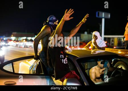Protesters chant as they ride in a car during a peaceful demonstration as communities continue to react to the shooting of Michael Brown in Ferguson, Missouri August 14, 2014. Missouri's governor Jay Nixon moved to ease tensions on Thursday after days of racially charged protests over the police shooting of Brown, an unarmed black teenager, putting the African-American captain of the Highway Patrol Ron Johnson in charge of security in the St. Louis suburb of Ferguson. REUTERS/Lucas Jackson (UNITED STATES - Tags: CIVIL UNREST CRIME LAW) - Stock Photo