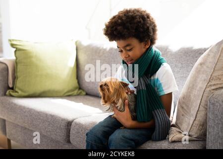 Young boy holding his puppy dog at home - Stock Photo