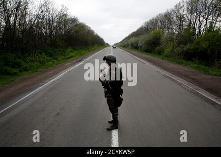 A Ukrainian soldier stands guard on a road at a check point near the village of Malinivka, southeast of Slaviansk, in eastern Ukraine April 29, 2014. REUTERS/Baz Ratner (UKRAINE - Tags: POLITICS CIVIL UNREST MILITARY TPX IMAGES OF THE DAY) - Stock Photo