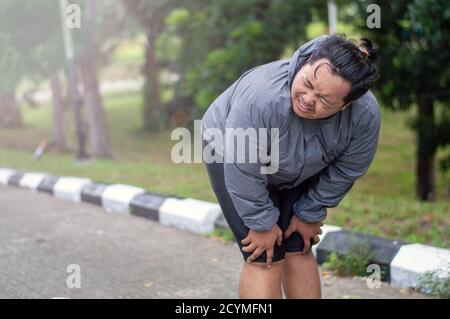 A Man Who Is Overweight Is Exhausted When He Is Trying To Lose Weight By Running In An Outdoor Park Stock Photo Alamy