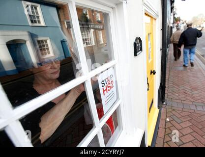 Susan Dorling poses as she places a HS2 protest sign in the window of her home in Great Missenden, south-west England January 9, 2012. The government is due to make its final decision on the controversial £17bn ($26.2bn) HS2 new high-speed rail line between London and Birmingham this week, local media reported. REUTERS/Darren Staples  (BRITAIN - Tags: POLITICS ENVIRONMENT TRANSPORT)