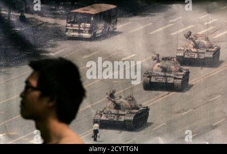 A man walks past a banner, printed with a photo of a man standing in front of tanks during the 1989 military crackdown on pro-democracy protesters around Beijing's Tiananmen Square, at Hong Kong's Victoria Park June 4, 2009. Tens of thousands of people are expected to attend a candlelight vigil later in the evening to commemorate those who died in the crackdown. REUTERS/Tyrone Siu (CHINA ANNIVERSARY CONFLICT POLITICS)
