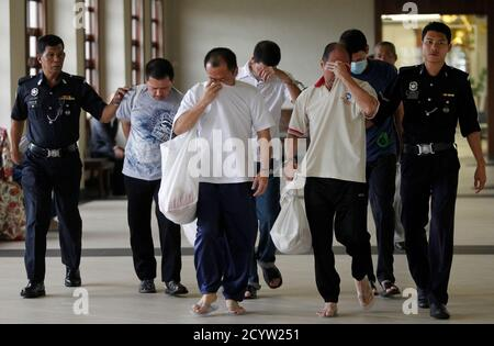 Flanked by police officers, Mexican national Luis Alfonso Gonzalez Villarreal (L), Singaporean Lim Hung Wang (2nd L), Luis Alfonso's brother Jose Regino (C), Malaysian Lee Boon Siah (2nd R) and another brother of Luis Alfonso, Simon, arrive at the court room in Kuala Lumpur May 17, 2012. The Gonzalez Villarreal brothers, Lim and Lee, on Thursday were sentenced to death by hanging after being found guilty of drug trafficking. REUTERS/Bazuki Muhammad (MALAYSIA - Tags: CRIME LAW) - Stock Photo
