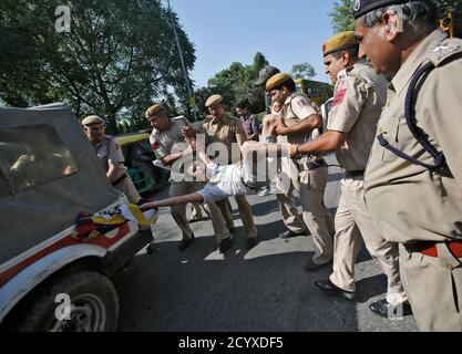 A Tibetan exile is detained by policemen during a protest near the hotel where China's President Xi Jinping is staying, while demonstrating against Xi?s visit to India, in New Delhi September 19, 2014. Hundreds of exiled Tibetans, carrying flags and banners, gathered outside the hotel in New Delhi on Friday, where Xi with his wife Peng Liyuan was staying. Police officials reached the spot and detained the demonstrators, who held noisy protests, demanding Free Tibet. REUTERS/Anindito Mukherjee (INDIA - Tags: CIVIL UNREST POLITICS) - Stock Photo