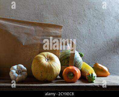 Organic fresh vegetables - yellow zucchini, round zucchini, bell peppers, garlic and eco friendly paper bag on gray background. Plastic free shoping - Stock Photo