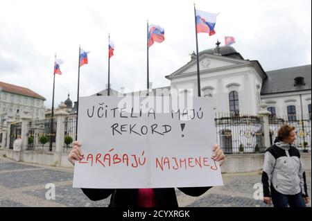 A teacher holds a sign during a one-day strike by local teachers seeking higher salaries and better work conditions, in front of the presidential palace in capital Bratislava September 13, 2012. The banner reads, 'Teachers hold a record, they earn the lowest salary.' REUTERS/Radovan Stoklasa (SLOVAKIA - Tags: BUSINESS EMPLOYMENT EDUCATION CIVIL UNREST) - Stock Photo