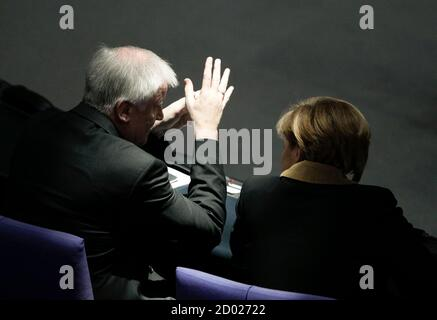 Bavarian state premier Horst Seehofer (L) speaks with German Chancellor Angela Merkel during Germany's Federal Assembly in Berlin, March 18, 2012. Joachim Gauck is poised to become Germany's third president in just two years on Sunday after winning support from the country's main political parties, but the feisty theologian may prove an awkward partner for Chancellor Angela Merkel.      REUTERS/Tobias Schwarz (GERMANY  - Tags: POLITICS ELECTIONS) - Stock Photo