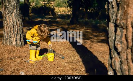 Young child is picking up plastic waste in the forest as a volunteer. Toddler and young children early environmental education concept. Plastic free