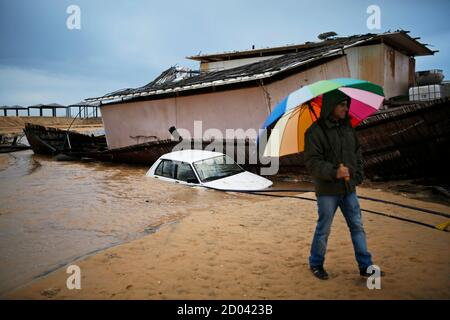 A man walks next to a car and a beach restaurant that sank into the sand following heavy rains and flooding on a beach of the Mediterranean sea near Kibbutz Nitzanim in southern Israel December 14, 2013. REUTERS/Amir Cohen (ISRAEL - Tags: ENVIRONMENT TPX IMAGES OF THE DAY)