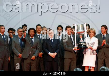 Real Madrid's goalkeeper Iker Casillas (3rd R, front) holds up the King's Cup trophy with Esperanza Aguirre (2nd R), president of Madrid regional government, as they pose for a picture with the Real Madrid soccer team in central Madrid May 11, 2011. REUTERS/Andrea Comas (SPAIN - Tags: SPORT SOCCER POLITICS)