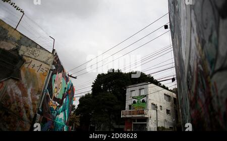 A man stands on the balcony of his house in front of graffiti-filled walls along 'Beco do Batman' (Batman's alley) in the Vila Madalena neighbourhood, which is a well-known open-air graffiti museum, in Sao Paulo April 20, 2014. Sao Paulo is one of the host cities for the 2014 World Cup soccer matches in Brazil. REUTERS/Nacho Doce (BRAZIL - Tags: SPORT SOCCER WORLD CUP TRAVEL SOCIETY)