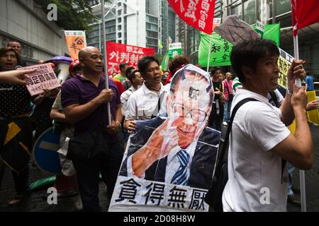 A dock worker holds a defaced picture of Hong Kong's richest man Li Ka-shing as he marches with others during a strike at Cheung Kong centre in Hong Kong, April 17, 2013. Striking dock workers at a port operator backed by Li failed to reach a deal for higher pay, prolonging a dispute that could cost the city its position as the world's third-largest container port. The picture reads, 'Unlimited Greed' REUTERS/Tyrone Siu (CHINA - Tags: BUSINESS EMPLOYMENT) - Stock Photo