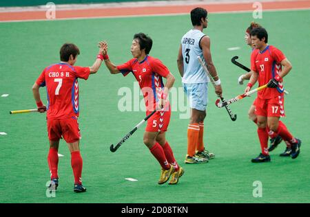 South Korea's Cho Suk-hoon (L) and Nam Hyun-woo (2nd L) celebrate after scoring their first goal as India's Rupinder Pal Singh (in blue) walks away during their 5th and 6th placement match in the Sultan Azlan Shah Cup hockey tournament in Ipoh, 200km (120 miles) north of Kuala Lumpur, May 15, 2011. REUTERS/Samsul Said (MALAYSIA - Tags: SPORT FIELD HOCKEY) - Stock Photo