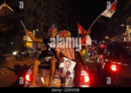 Protesters holding a crossed-out picture of President Mohamed Mursi chant slogans and wave flags as they ride on the back of a car in Alexandria June 30, 2013. Protesters and members of the Tamarod 'rebel' movement on Saturday called for a mass protest as Mursi marks one year in power, to press for early presidential elections. Mass demonstrations across Egypt on Sunday may determine its future, two and half years after people power toppled a dictator they called Pharaoh and ushered in a democracy crippled by bitter divisions. REUTERS/Asmaa Waguih (EGYPT - Tags: POLITICS CIVIL UNREST) - Stock Photo