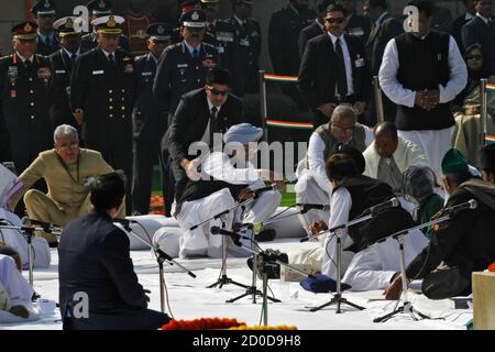 India's Prime Minister Manmohan Singh (wearing blue turban) is helped up by his bodyguard after a prayer meeting to pay homage to Mahatma Gandhi on his death anniversary at Rajghat in New Delhi January 30, 2012. Mahatma Gandhi, father of the Indian nation, was assassinated in 1948. India observes Gandhi's death anniversary as Martyrs' Day. REUTERS/B Mathur (INDIA - Tags: POLITICS OBITUARY ANNIVERSARY) - Stock Photo
