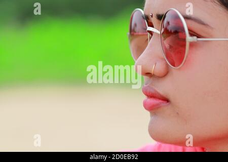 macro profile view woman face closeup gorgeous pink lips in Natural summer fashion wearing sunglasses. concept to care ( skin , eyes ) upper body part