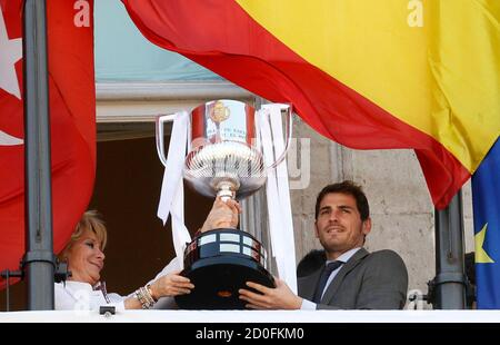Real Madrid's goalkeeper Iker Casillas (R) holds up the King's Cup trophy with Esperanza Aguirre, president of Madrid regional government, as they pose at a balcony with other team members in central Madrid May 11, 2011. REUTERS/Andrea Comas (SPAIN - Tags: SPORT SOCCER POLITICS)