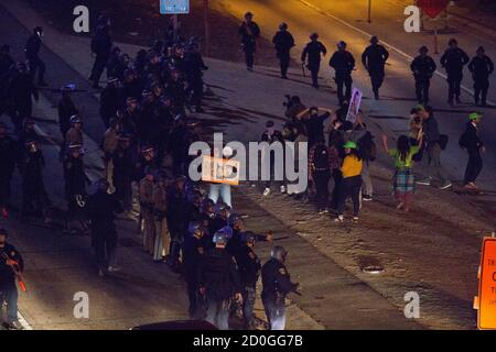 California Highway Patrol officers clear the 101 freeway from protesters in Los Angeles, California, following Monday's grand jury decision in the shooting of Michael Brown in Ferguson, Missouri, November 25, 2014. U.S. President Barack Obama said on Tuesday anyone who destroys property in rioting against a Missouri grand jury's decision should be prosecuted, urging Americans upset by the court to work together to improve race relations.  REUTERS/Mario Anzuoni  (UNITED STATES - Tags: CRIME LAW POLITICS CIVIL UNREST)