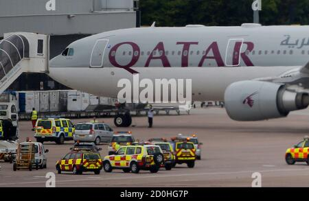 A Qatar Airways aircraft is seen surrounded by emergency vehicles at Manchester airport in Manchester, northern England August 5, 2014. A British fighter jet escorted a passenger plane into Manchester airport on Tuesday afterthe pilot reported that a suspect device was possibly on board, police said.   REUTERS/Andrew Yates (BRITAIN  - Tags: TRANSPORT CRIME LAW MILITARY TRAVEL) - Stock Photo