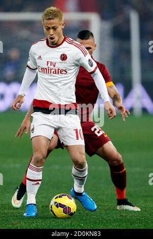 AS Roma's Jose Holebas (R) challenges AC Milan's Keisuke Honda during their Italian Serie A soccer match at the Olympic stadium in Rome, December 20, 2014. REUTERS/Giampiero Sposito (ITALY - Tags: SPORT SOCCER) - Stock Photo