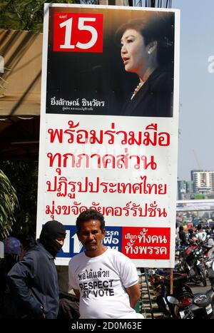 A pro-government supporter stands in front of a portrait of Thailand's Prime Minister Yingluck Shinawatra, during an election campaign in Nonthaburi province, on the outskirts of Bangkok January 31, 2014. Thailand goes to the polls on Sunday, but the usual pre-election buzz, banners and loud-hailers on the backs of trucks are noticeable by their absence in the capital, Bangkok. REUTERS/Chaiwat Subprasom (THAILAND - Tags: POLITICS CIVIL UNREST ELECTIONS) - Stock Photo