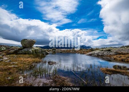 A small lake during the Trolltunga hike in Norway with beautiful sky. Stock Photo