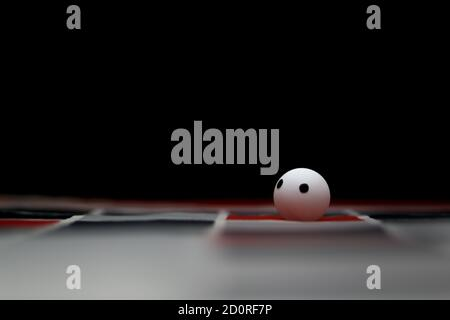 Alone and stranded concept. A white ball facing up with blurry geometric fabric based and black background. Selective focus.