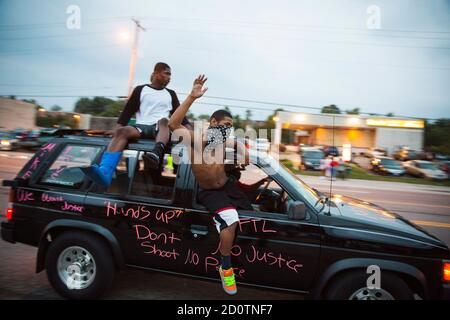 Protesters hang out of a car as they honk their horn and chant during ongoing demonstrations in reaction to the shooting of Michael Brown in Ferguson, Missouri August 16, 2014. Missouri Governor Jay Nixon declared a state of emergency and imposed a curfew in Ferguson on Saturday following a week-long series of racially charged protests and looting over the shooting of the unarmed black teenager by a white police officer. REUTERS/Lucas Jackson (UNITED STATES - Tags: CIVIL UNREST CRIME LAW POLITICS TPX IMAGES OF THE DAY) - Stock Photo