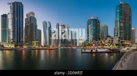 Evening view of Dubai Marina skyscrapers including Cayan Tower, an affluent residential neighbourhood in Dubai, UAE, United Arab Emirates - Stock Photo