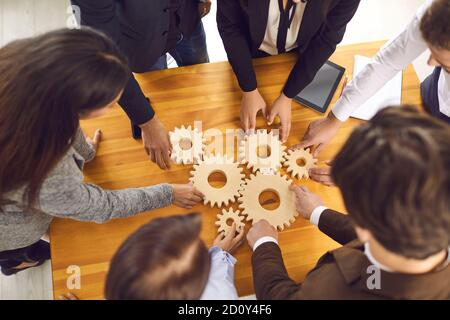 Startup team joining cogwheels as metaphor for teamwork, management and finding business solutions