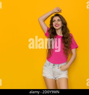 Relaxed young woman in pink t-shirt and jeans shorts leans on a yellow wall, holds hand over head and looks away. Three quarter length studio shot. - Stock Photo