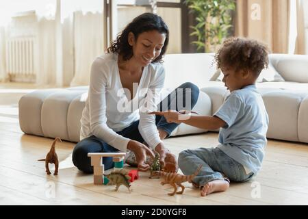 Young african ethnicity woman playing with boy at home.