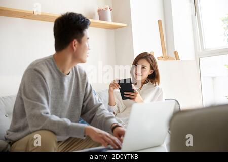 happy and relaxed young asian couple chatting conversing while staying at home