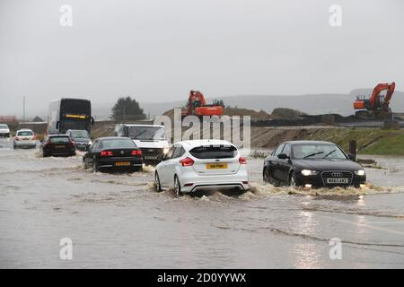 Cars make their way through a flooded road in Claudy, County Londonderry. The UK's wet weekend will continue as a weather warning for rain across parts of Wales and England has been extended. - Stock Photo