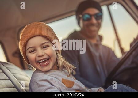 Cheerful Family Having Fun Together in the Car. Enjoying Road Trip. Father with Pleasure Teaching his Little Son to Driving Auto. Happy Fatherhood.