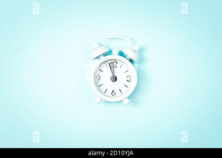 White vintage style alarm clock showing five minutes left untill midnight over blue background. New Year advent.