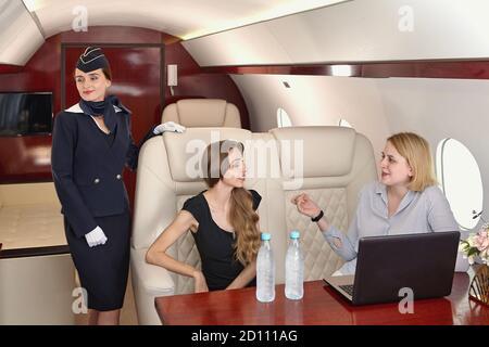 Air stewart serves passengers inside the airplane. A flight attendant stands near the passenger seats on board a corporate jet. Young women communicat