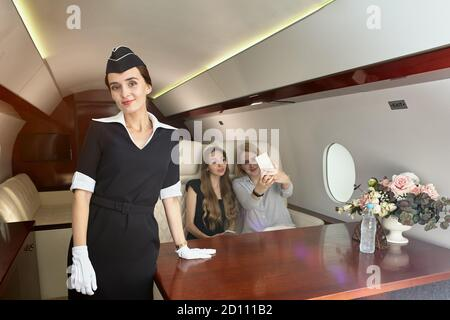Air hostess serves passengers inside the plane. Beautiful flight attendant in the passenger cabin of the aircraft on the background of young women in