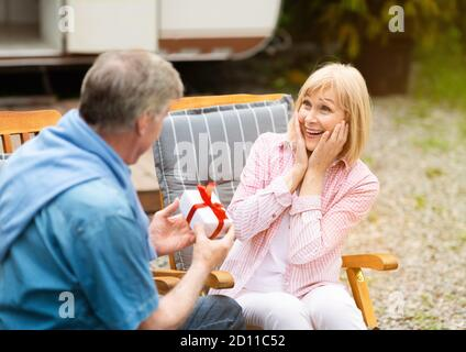 Senior man giving birthday gift to his surprised wife near RV in counryside