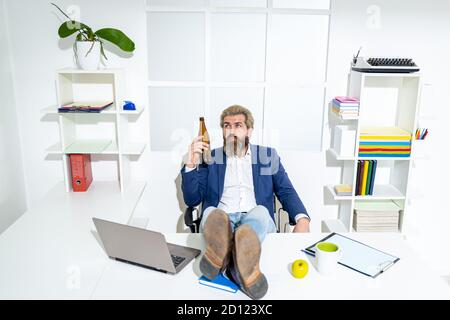 Sad office worker desperate about unfair dismissal losing job. After hard work. Businessman hold a beer bottle. - Stock Photo