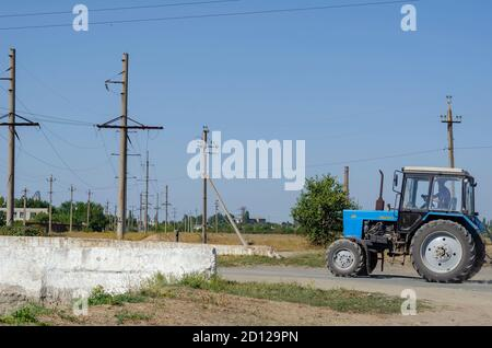 Nikolaev, Ukraine - September 15, 2020: A blue tractor drives along a rural road. The inscription in Russian means the name of the tractor. Agricultur - Stock Photo