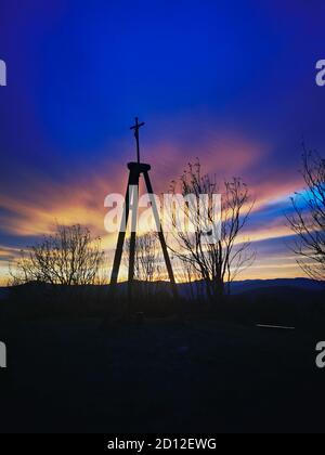 Sunrise in the Bieszczady mountains. Cross on top of the mountain illuminated by light. - Stock Photo