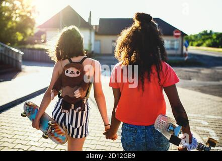 Rear view of teenager girls friends with skateboards outdoors in city.