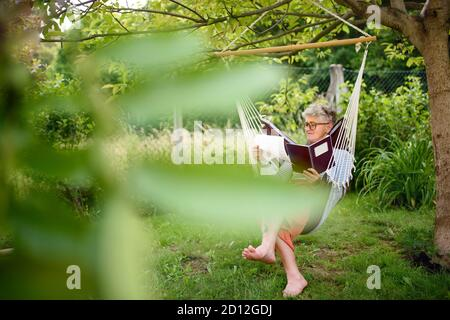 Portrait of active senior woman working outdoors in garden, home office concept.