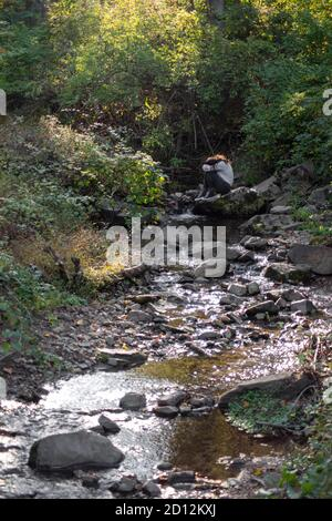 Sad young man sits alone by a forest stream covering his face.