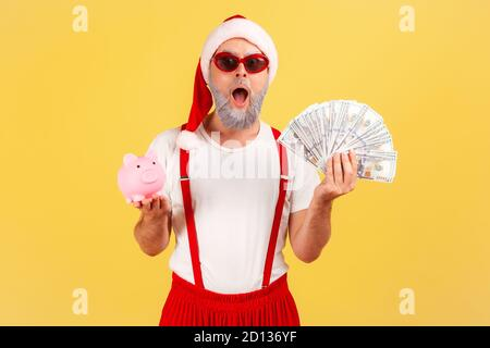 Extremely shocked adult man in stylish sunglasses and santa claus hat holding piggy bank and dollar banknotes looking at camera, deposit, cashback. In
