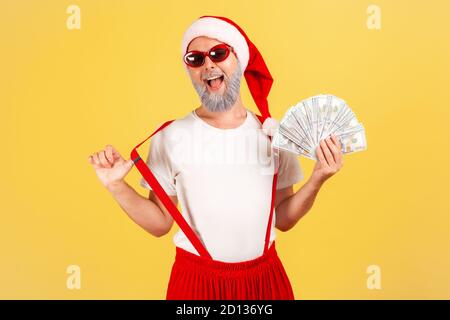 Excited positive elderly man in santa claus hat and sunglasses showing fan of dollars looking at camera with extremely satisfied expression, betting.